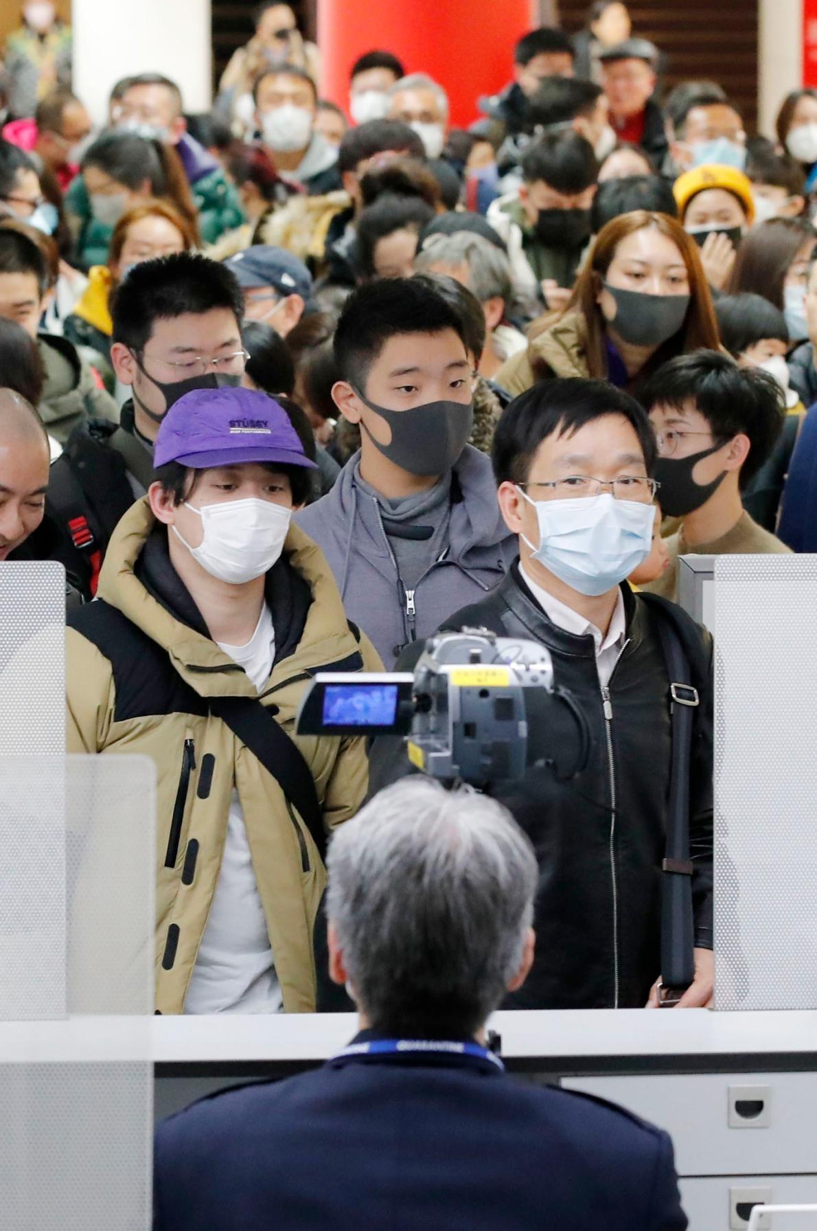 2020年1月23日,從新型冠狀病毒肺炎爆發起源地中國武漢飛抵日本的旅客,正通過東京成田機場的檢疫。前景中架設的是溫度監控儀器,用以檢查旅客的體溫。PHOTOGRAPH BY KYODO VIA AP IMAGES