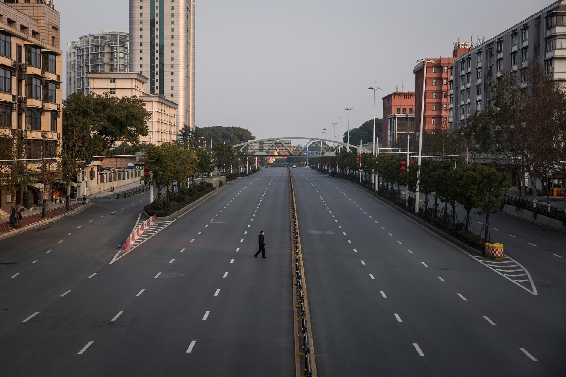 2020年2月3日,一名男子穿越中國武漢一處空蕩蕩的高速公路。中國武漢冠狀病毒感染的死亡人數已攀升至超過1000人。其他國家也有通報病例,包括美國、加拿大、澳洲、日本、南韓、印度、英國、德國、法國等。PHOTOGRAPH BY GETTY IMAGES