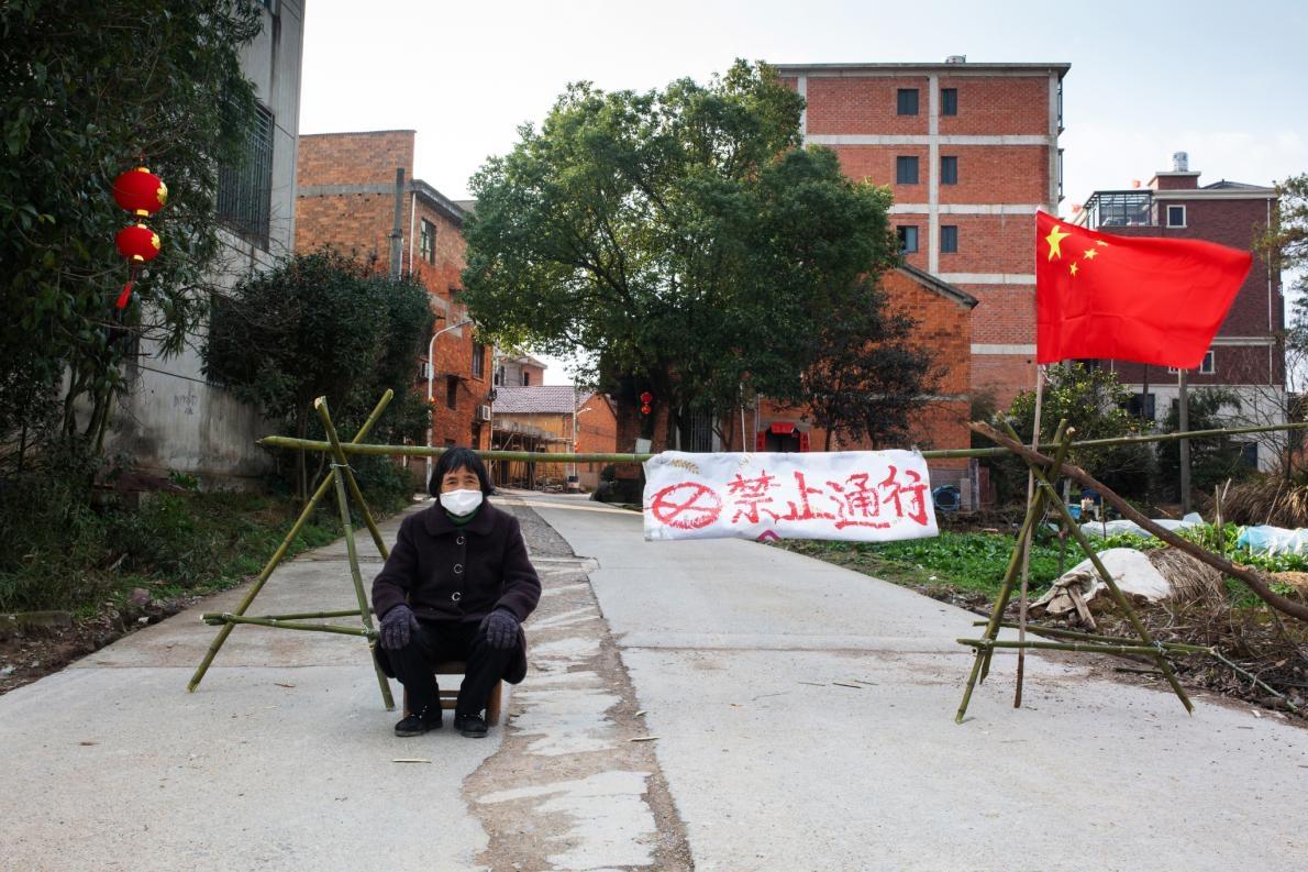 郎村讓老人家守在通往鎮上的三個入口。一位居民坐在其中一處入口,該處用中國國旗和一塊寫著「禁止通行」的布告擋住路。PHOTOGRAPH BY ROBAN WANG, NATIONAL GEOGRAPHIC