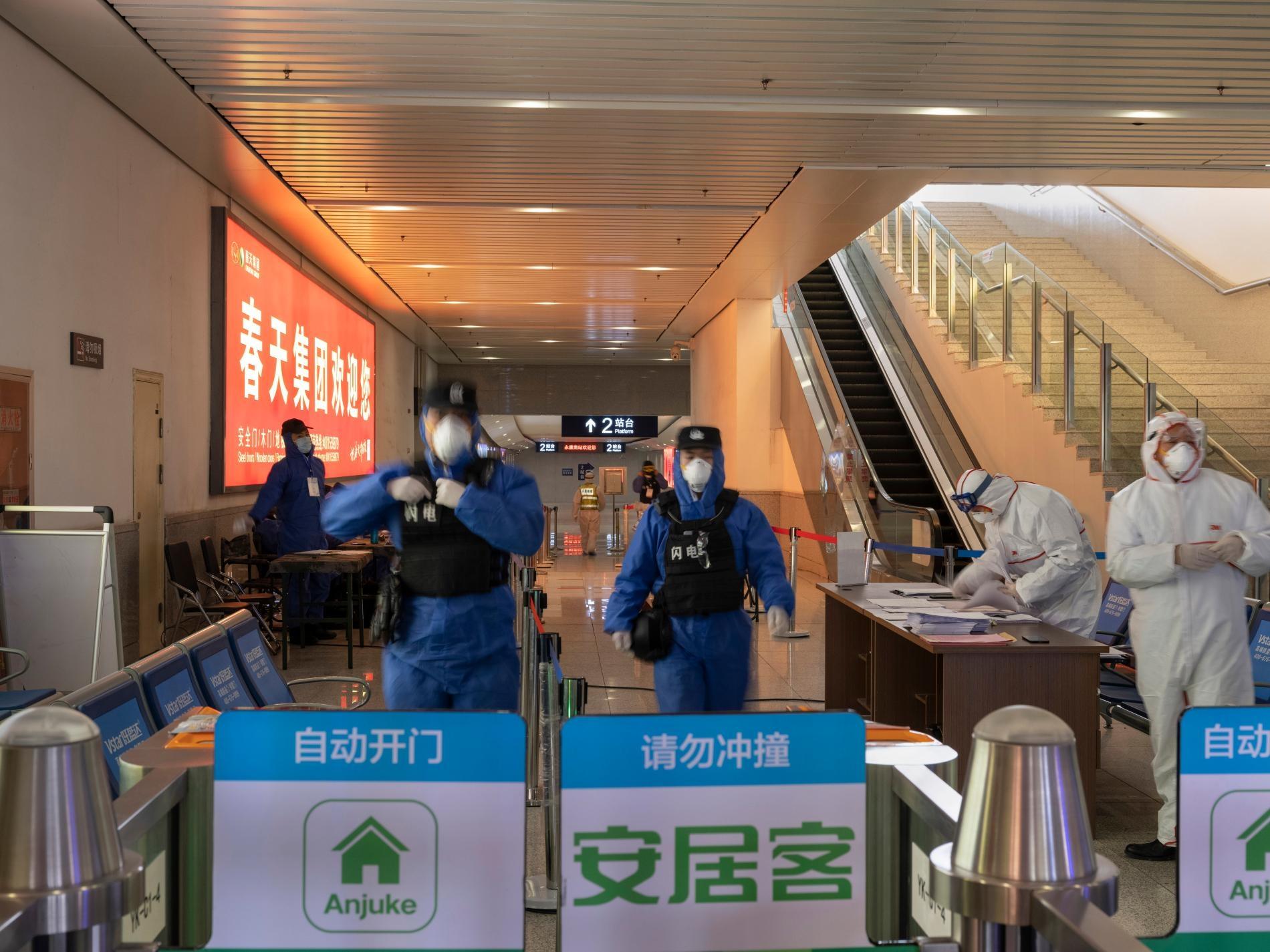 2月9日,警察與衛生人員守在高鐵站其中一處出口。全國各地還在營運的車站,每個出入口都要幫旅客量體溫。旅客若是發燒超過攝氏37.3度,就要被帶到健康機構。PHOTOGRAPH BY ROBAN WANG, NATIONAL GEOGRAPHIC
