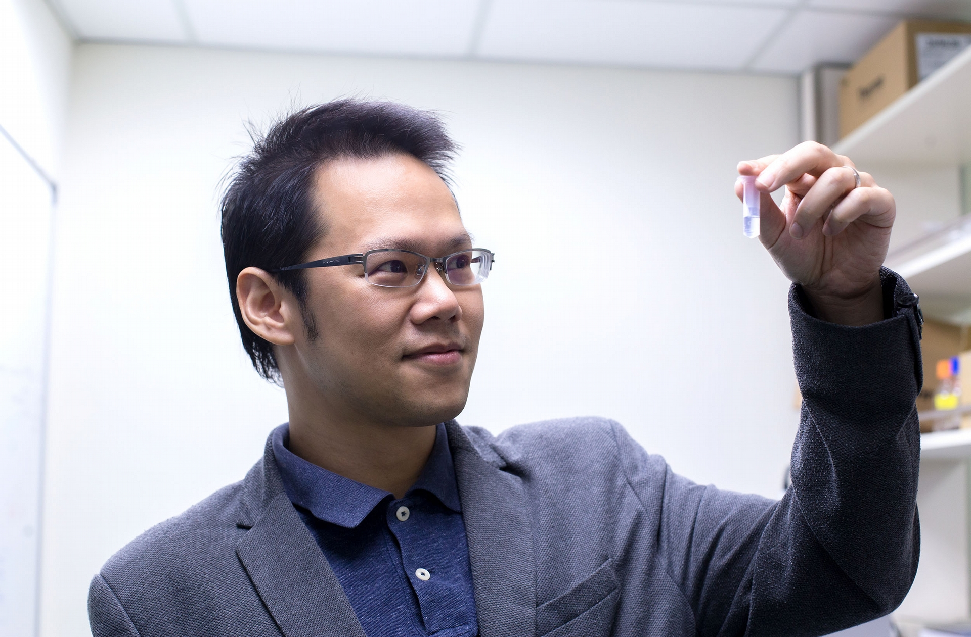 胡哲銘看著自己發明的冠狀病毒奈米疫苗,小小的容器裡充滿了 10,000,000,000,000 個薄殼中空奈米粒子。 <br>攝影│林洵安