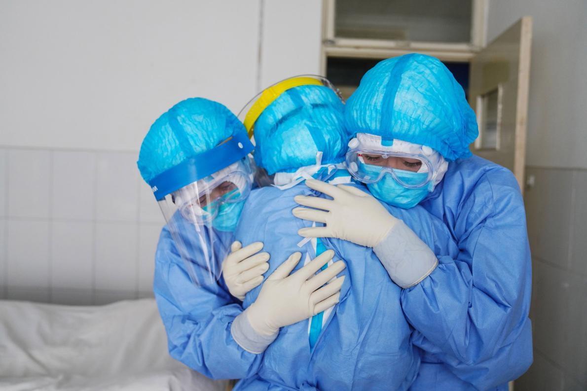 在中國山東省鄒平市的一間醫院裡,醫護人員在隔離病房內擁抱彼此。PHOTOGRAPH BY STR/AFP VIA GETTY IMAGES