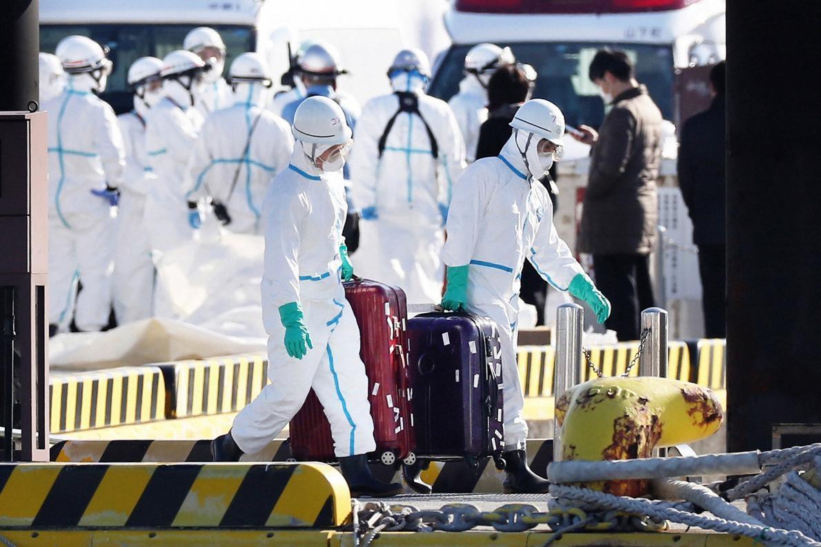 身著防護裝備的衛生官員從停泊在日本橫濱的鑽石公主號遊輪上帶出行李箱,大眾普遍認為這些行李箱的主人,就是驗出冠狀病毒陽性後從船上撤離送醫的乘客。PHOTOGRAPH BY ASAHI SHIMBUN, GETTY IMAGES