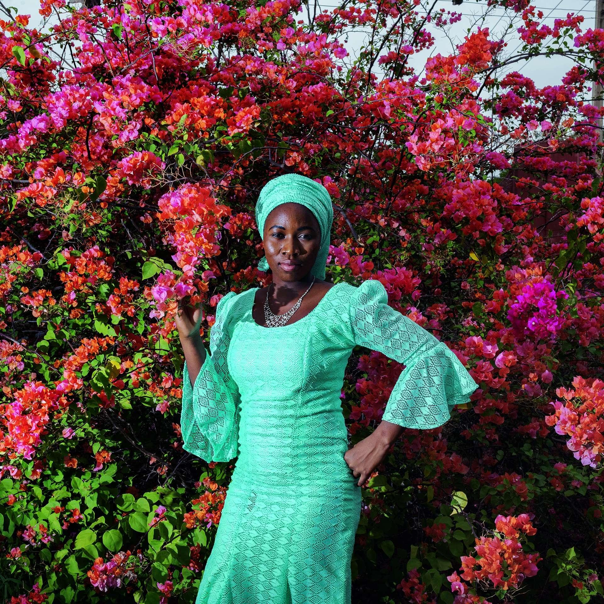 艾思黛.伍斯曼站在位於奈及利亞東北部的學校宿舍後方,她和其他一百多名來自奇博克的學生在這裡生活和讀書。這些年輕女性正在準備大學入學考,並計畫未來要投入商業、醫學和人權法領域。攝影:貝內迪克特.庫森 BÉNÉDICTE KURZEN