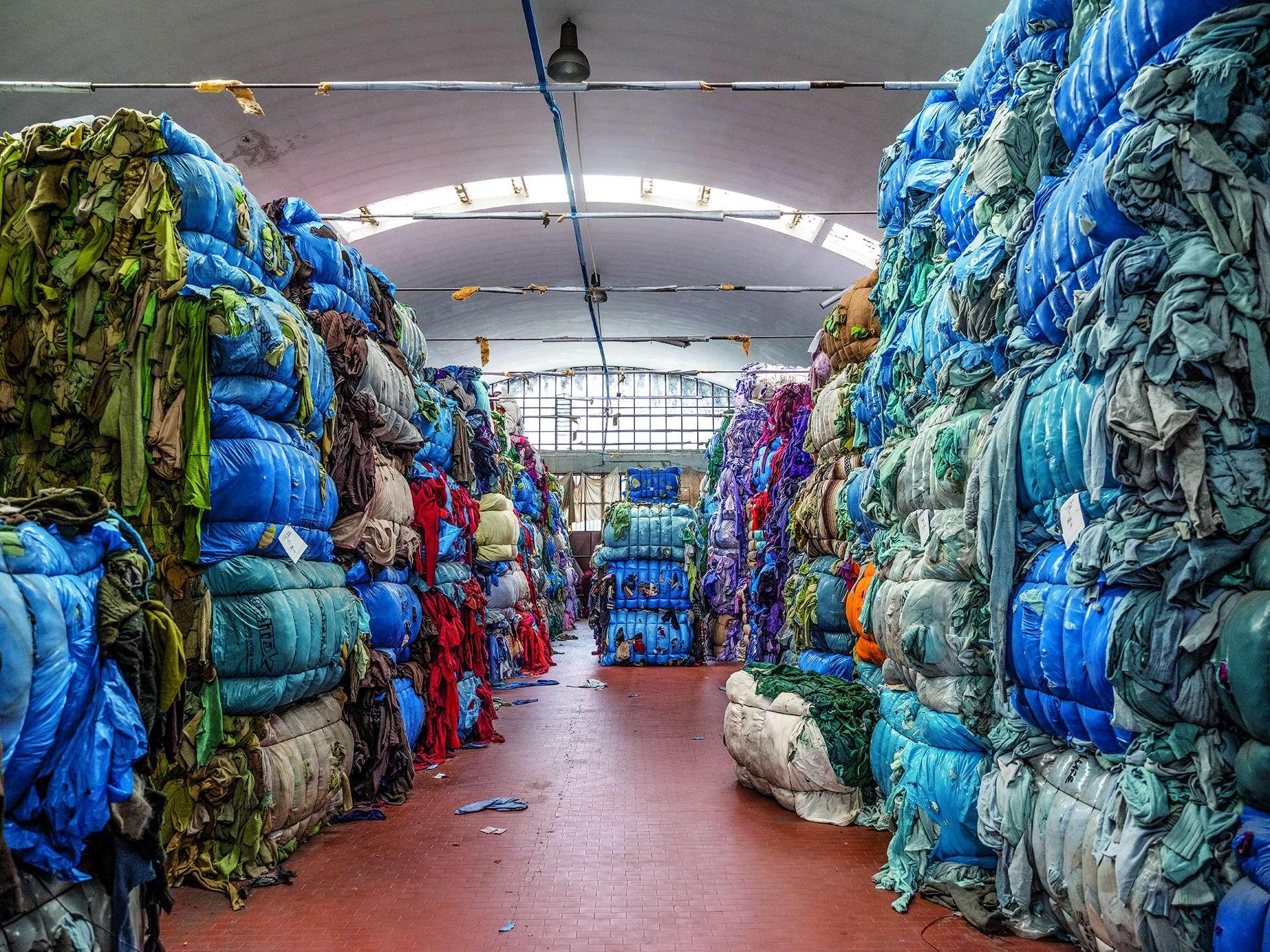 義大利普拉托一間公司的回收場,成捆的廢棄布料經過處理後將用來製作成新衣服,這是循環經濟的一個實踐案例。攝影: 盧卡. 洛卡泰利 LUCA LOCATELLI