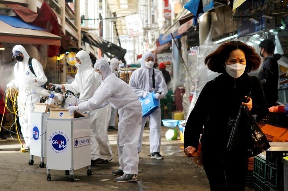 2020年2月26日,消毒公司的員工在幫南韓首爾一處傳統市場消毒,旁邊一名女性戴著口罩,以免感染新型冠狀病毒。PHOTOGRAPH BY KIM HONG-JI, REUTERS