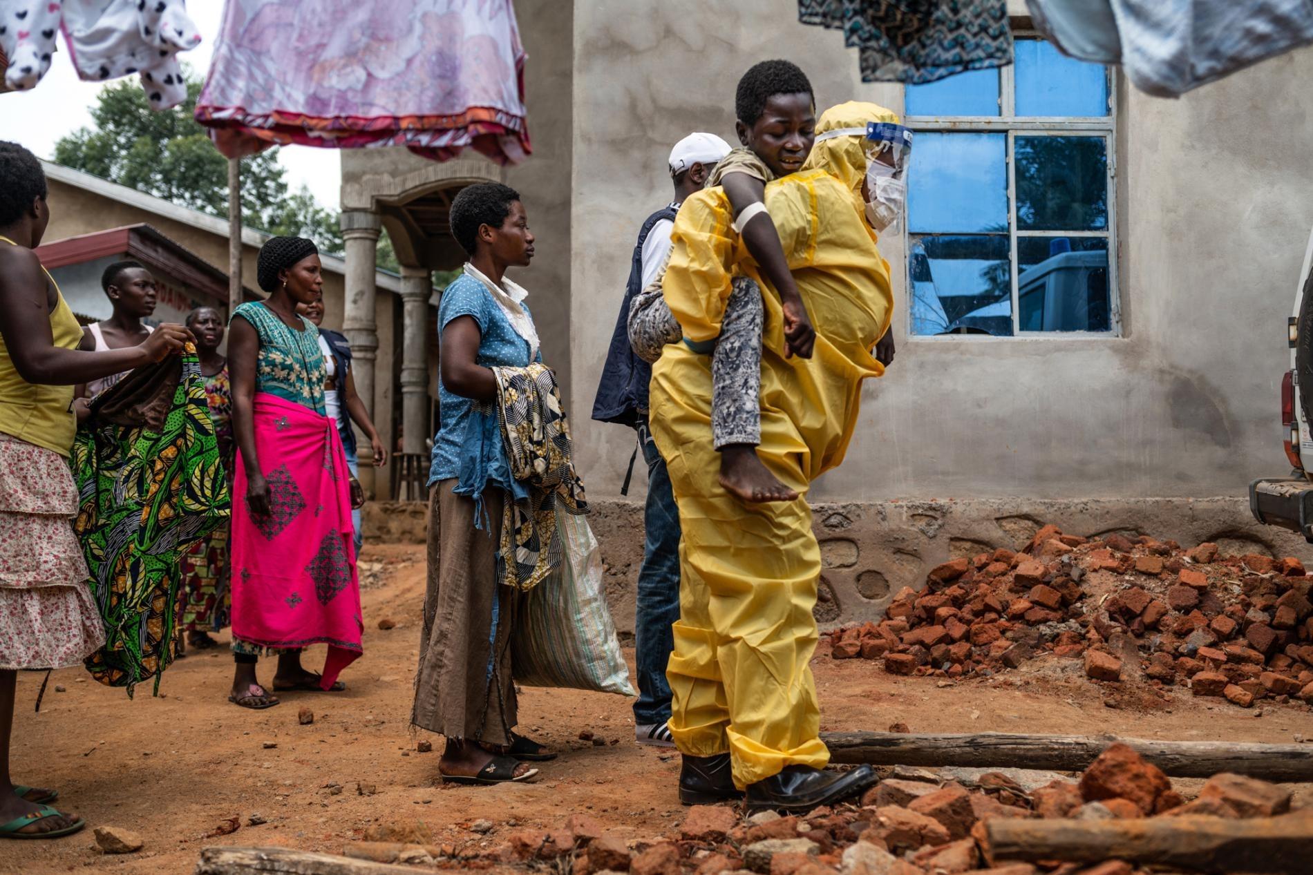 去年在貝尼,一名醫護人員揹著14歲的卡庫萊.卡文迪瓦(Kakule Kavendivwa)走向一輛停在路邊的救護車。卡庫萊的姊妹在前一天曾帶他去附近的衛生中心,但那裡的團隊鼓勵他們去治療中心時,他們就逃走了。衛生中心向找到那個家庭的世界衛生組織發出警報。跟社區醫療外展人員討論數小時後,他們允許一輛救護車送卡庫萊去治療。PHOTOGRAPH BY NICHOLE SOBECKI