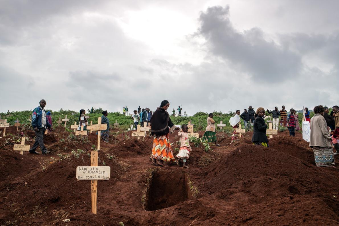 2019年3月2日,厚厚雲層之下,成群結隊的哀悼者在新墳之間慢慢行走,當時他們正走去參加DRC布滕博的基塔圖巴墓園裡50歲員警塔布.阿姆利.艾曼紐(Tabu Amuli Emmanuel)的葬禮。這處墓園坐落於山丘上,可俯瞰布滕博這座DRC東北部最大的城市。在剛果與伊波拉病毒的最新戰役中,罹難者就於此處安息。PHOTOGRAPH BY NICHOLE SOBECKI