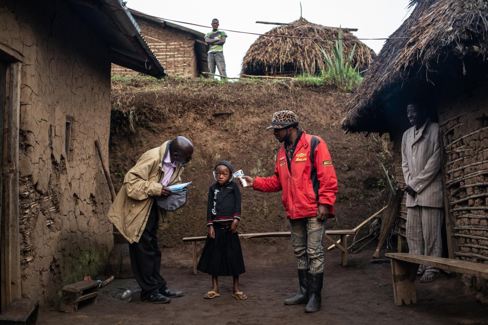 2019年,一個WHO團隊在瓦亞納鎮為7歲的康福美.馬斯卡.穆格漢伊拉(Confirme Masika Mughanyira)檢查體溫,該鎮位於DRC布滕博兩小時車程處。因為伊波拉疫情,康福美失去了雙親、哥哥及妹妹。身為家裡唯一一名倖存者,她現在由親戚照料。PHOTOGRAPH BY NICHOLE SOBECKI