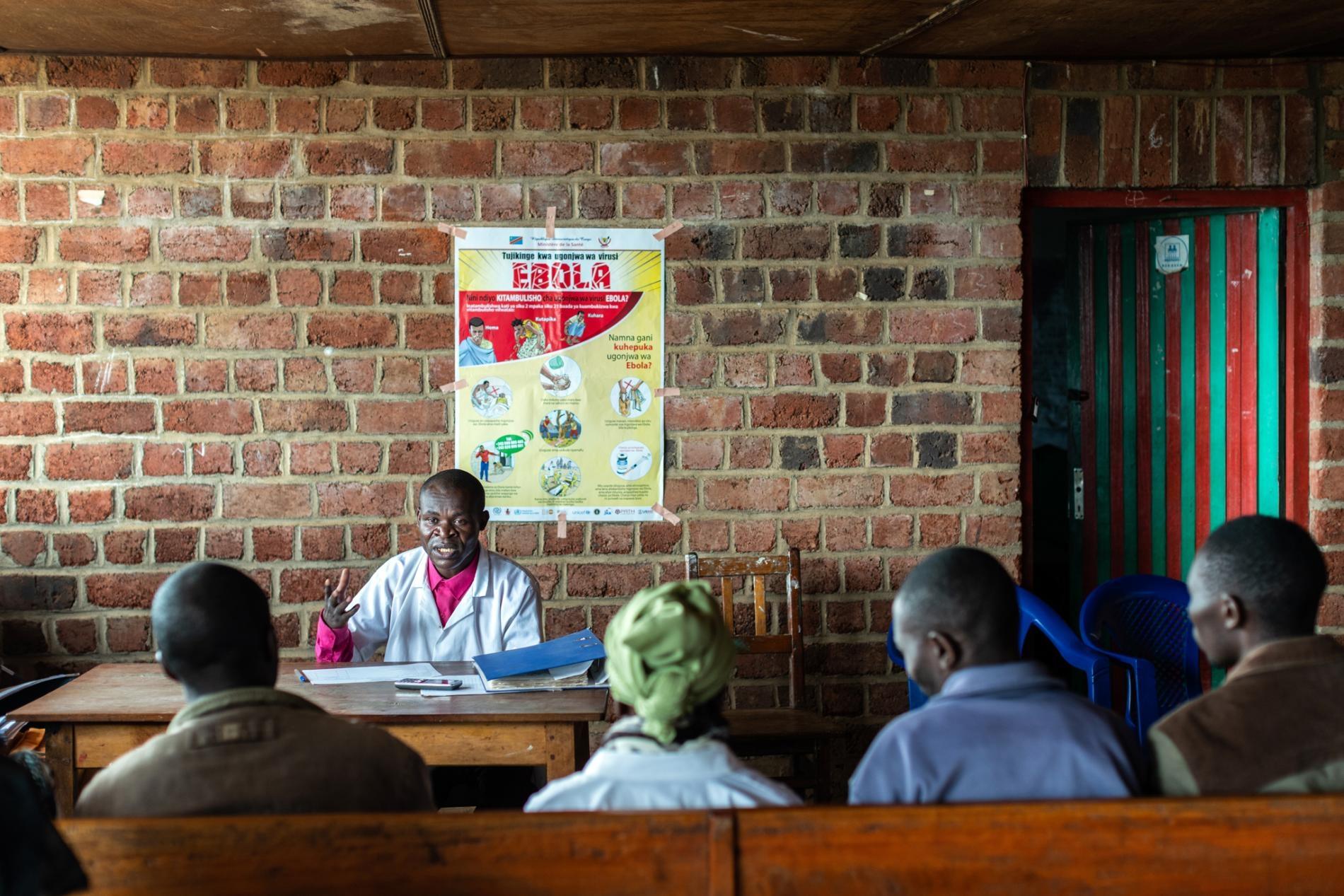 2019年3月4日,在DRC炯多鎮外,當地衛生團隊與社區醫療外展人員在一天的實地工作後互相交流,討論集體進展與面臨的挑戰。WHO已經在大城市外,像炯多這樣的區域設立數個伊波拉反應營,小型群聚的伊波拉病患會出現在這種區域。炯多位於布滕博往維龍加方向的1.5小時車程處。PHOTOGRAPH BY NICHOLE SOBECKI