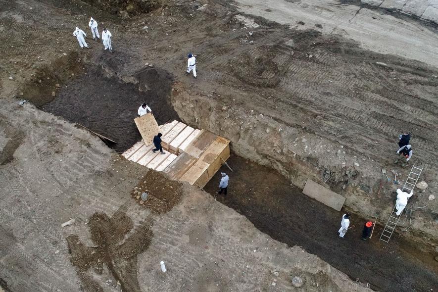 2020年4月9日,工作人員身著個人防護裝備埋葬屍體。過去紐約市驗屍官在將遺體送至哈特島市立公墓暫時下葬前,會保留遺體兩個月。4月9日後則減為兩週。PHOTOGRAPH BY JOHN MINCHILLO, AP