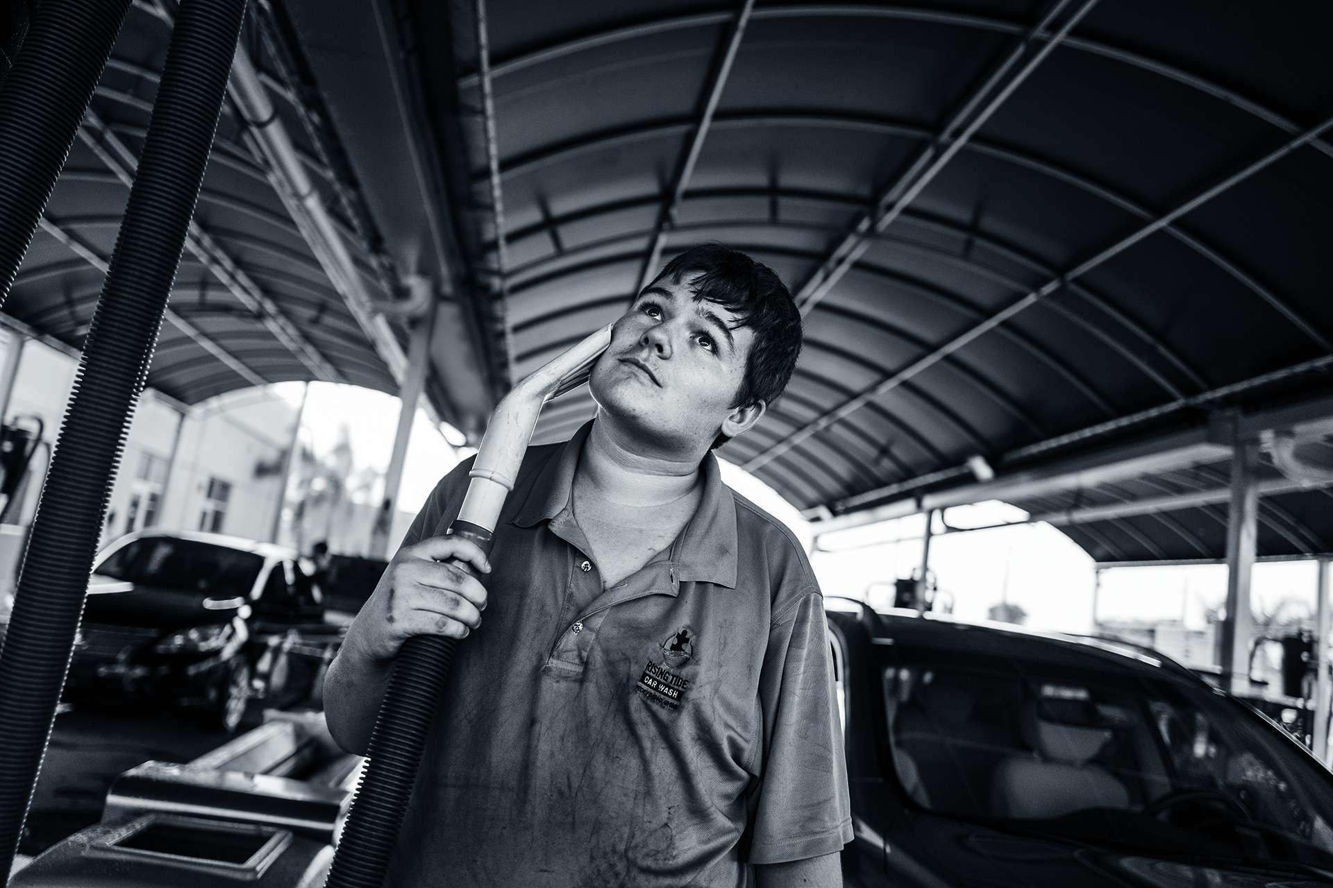 在佛羅里達州馬蓋特市的「漲潮洗車」,19歲的路克.贊達用吸塵器的吸嘴輕撫臉頰。湯姆.德瑞與他的父親開創了這家公司,並僱用他的弟弟與其他自閉症人士。協助自閉症成人找工作的家庭企業愈來愈常見。 PHOTO: LYNN JOHNSON