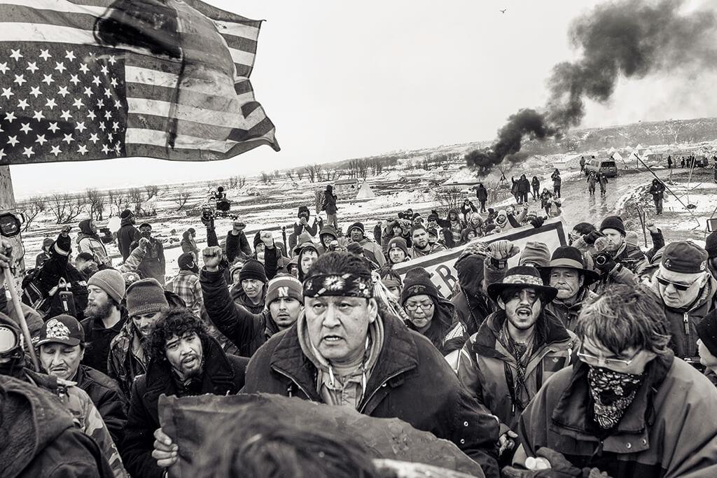反對興建達科他輸油管的示威者在2017年2月執法單位下達驅逐令後,離開立岩印第安保留地附近的歐切堤撒科溫營地。攝影師霍蘇埃. 雷瓦斯發起「悍然而立」計畫,探索原住民的身分認同、主權和堅韌不拔。抗議輸油管的行動激發許多美國原住民參加2018年的期中選舉,角逐公職。攝影: 霍蘇埃.雷瓦斯墨西加人和 歐托密人