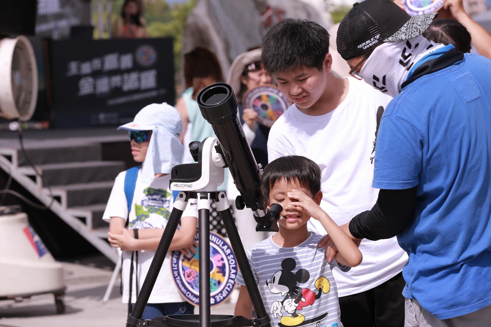 小朋友於嘉義市日環食活動現場用望遠鏡觀測太陽。
