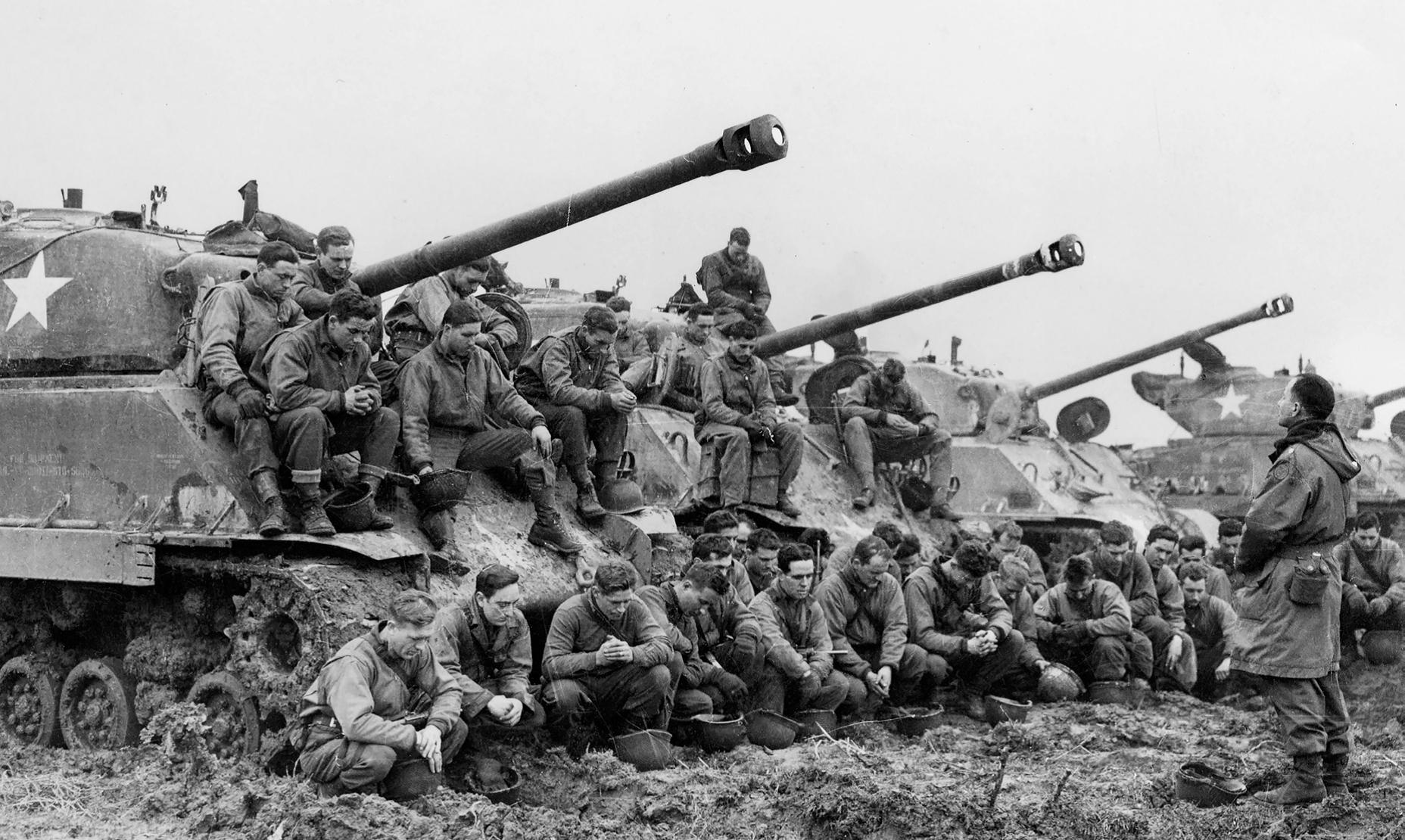 1945年,美軍隨軍牧師喬治・道姆(George F. Daum)少校在雪曼戰車兵準備進軍德國之前帶領他們祈禱。