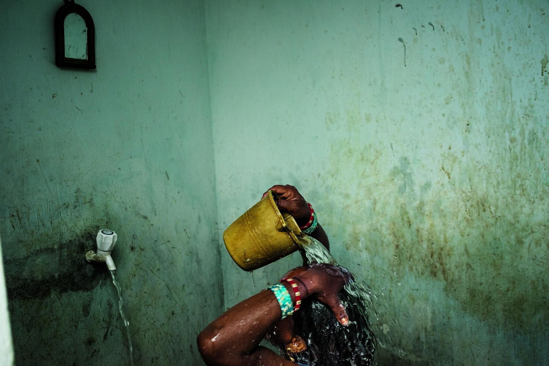 一名女子在印度東部奧里薩邦的布巴內斯瓦爾市附近洗澡。印度大部分的都市家庭──以及82%的農村家庭──都沒有自來水。PHOTO: ANDREA BRUCE