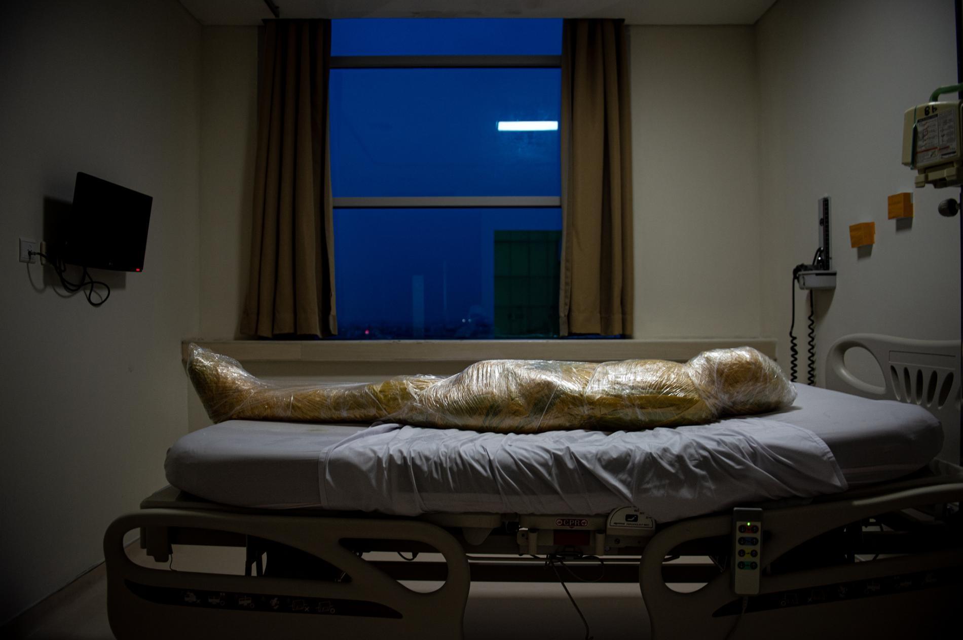 疑似COVID-19罹難者的遺體放在印尼的一間醫院。該病患死亡後,護理師用層層塑膠膜包裹遺體並塗抹消毒劑,以預防病毒傳播。PHOTOGRAPH BY JOSHUA IRWANDI