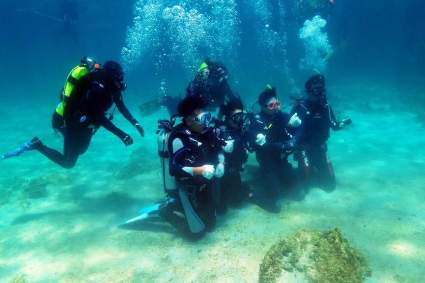 第一次潛水重裝下水總是令人興奮且緊張,因學員仍未習慣在海中的零重力,<br>因此仍須與潛伴之間互相抓緊以穩定姿勢。攝影:朱雲瑋