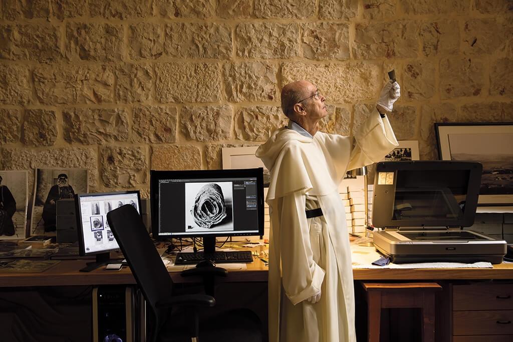 道明會神父尚-米榭.迪.特拉貢在耶路撒冷的法國聖經暨考古學院中檢視檔案照片。這裡的學者主導了死海古卷的搜尋工作,這批古卷也是目前發現最古老的聖經文本。   攝影:保羅.維佐尼 Paolo Verzone