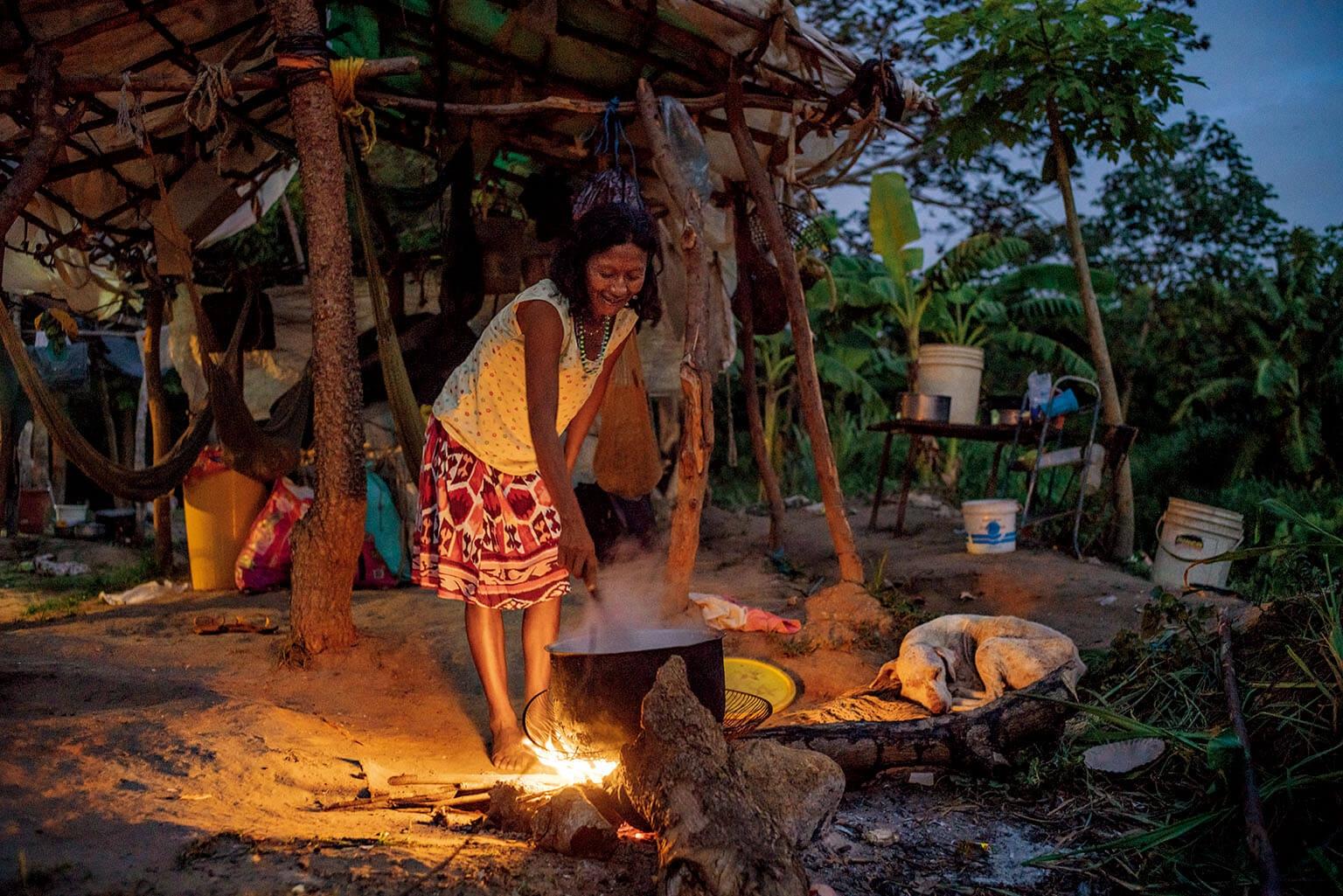 前往巴西邊界途中,瓦老族婦女在委內瑞拉的瓜雅納城附近以營火煮晚餐。許多瓦老人走路或搭便車抵達巴西境內的收容所,這段旅程可耗時多日。攝影: 菲德利科.里歐斯 FEDERICO RIOS