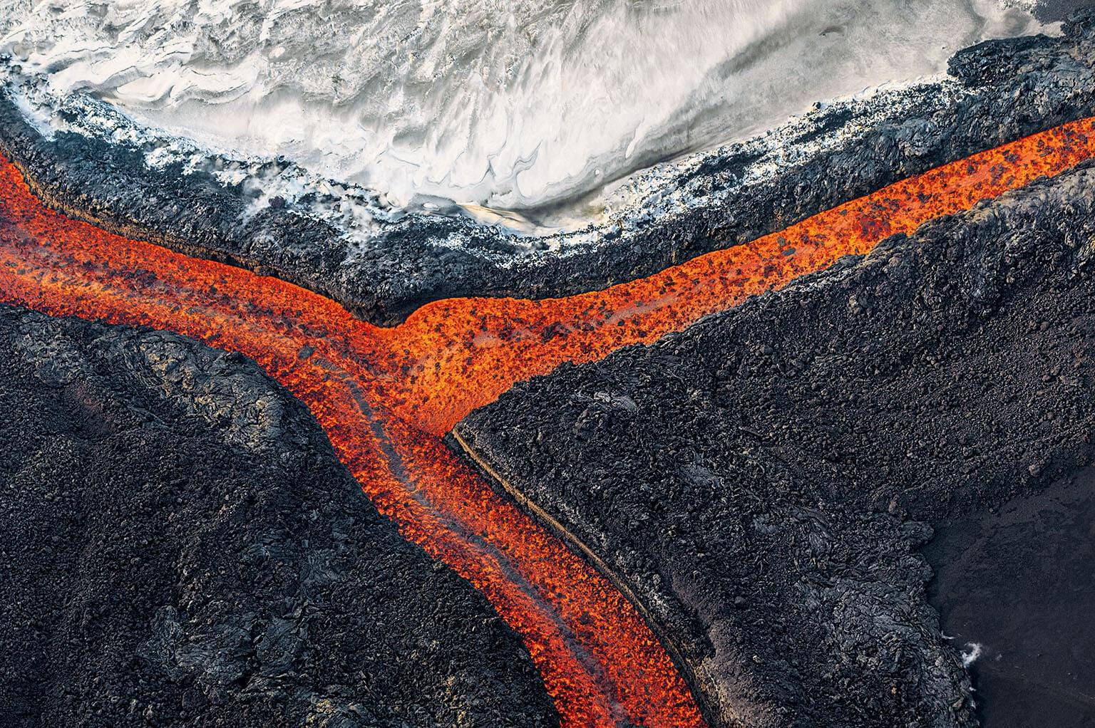 熔岩流在扎爾巴奇克火山白雪覆頂的山峰附近匯流(由右向左)。這座火山位於堪察加半島的克柳切夫自然公園。