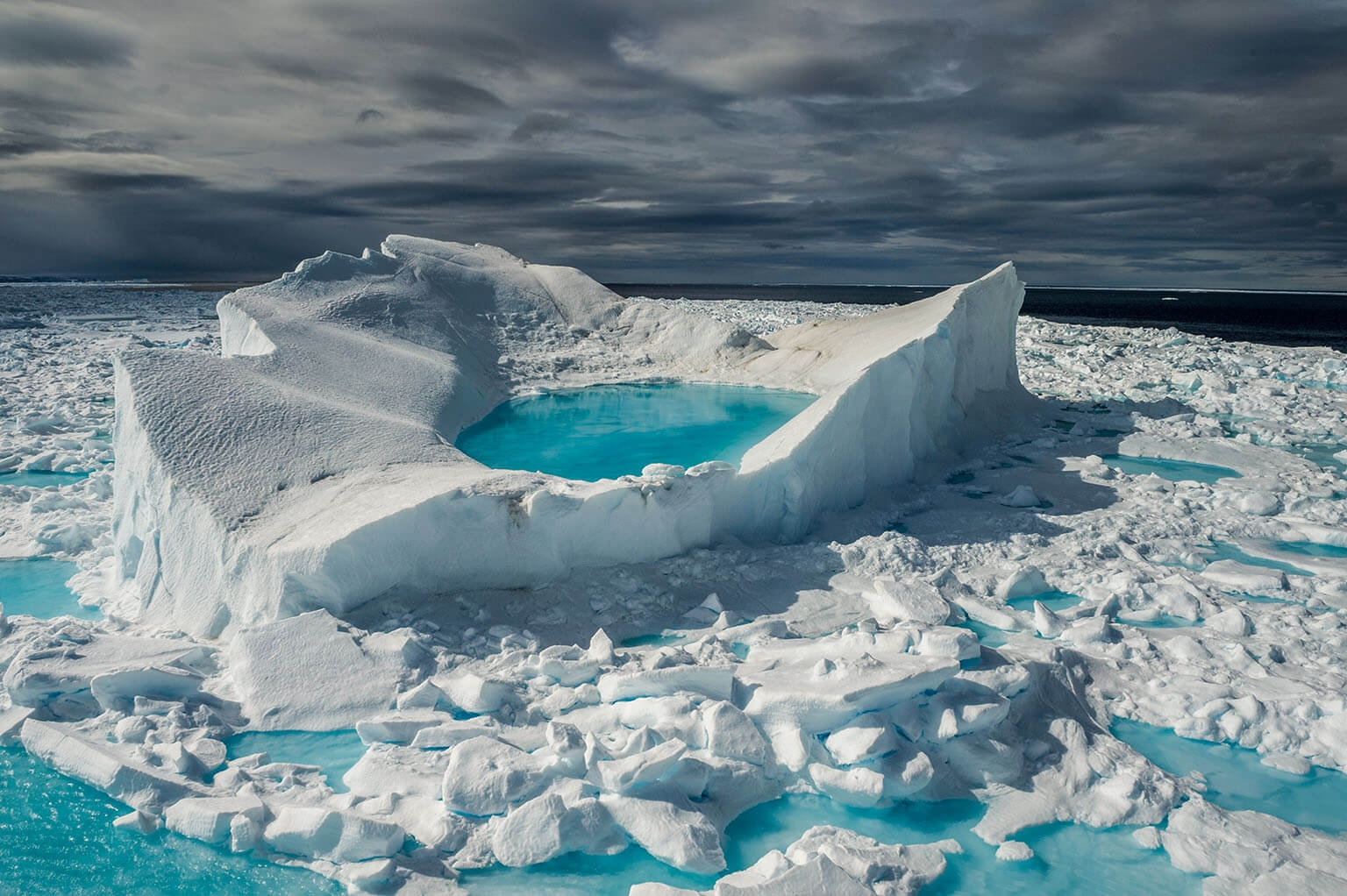 6月的陽光讓加拿大巴芬島北部沿海的冰與雪化為清澈碧綠的池塘。北極多年海冰(在炎熱的夏季也不融化的冰)的面積已經大幅縮減。BRIAN SKERRY