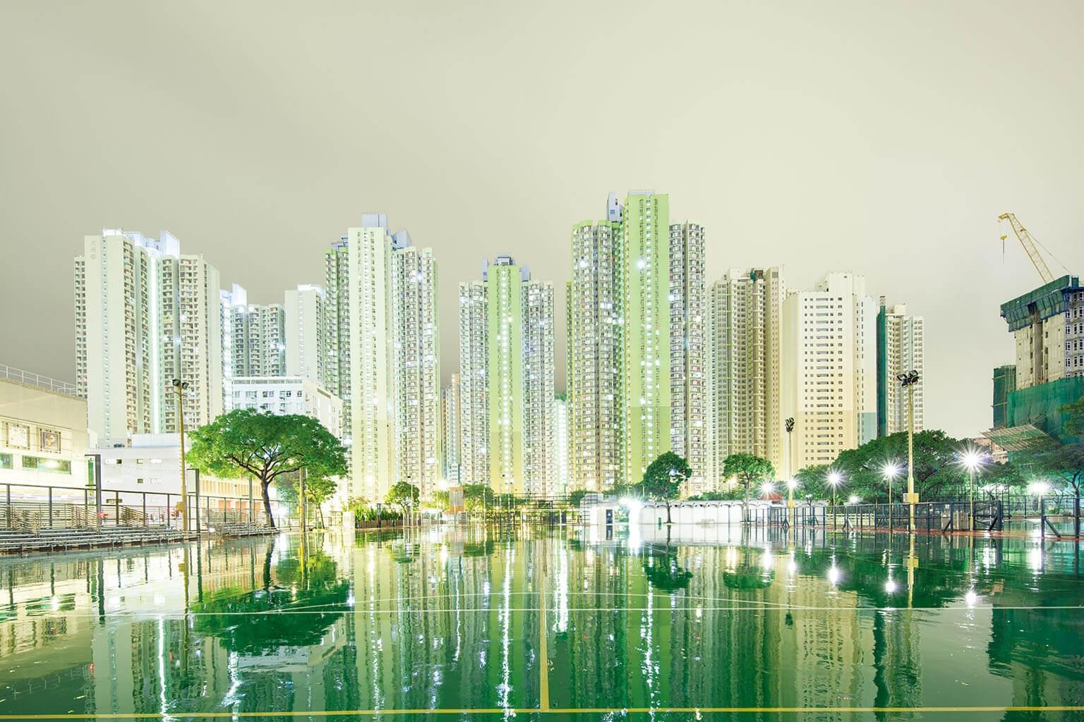 香港是世界上人口最稠密的城市之一,面積僅1103平方公里的土地上住著700萬人。這張在雨天用長時間曝光拍攝的照片呈現了部分天際線,投映在這座遊樂場因颱風而浸溼的地面上。 PHOTO: SPREEPHOTO/GETTY IMAGES