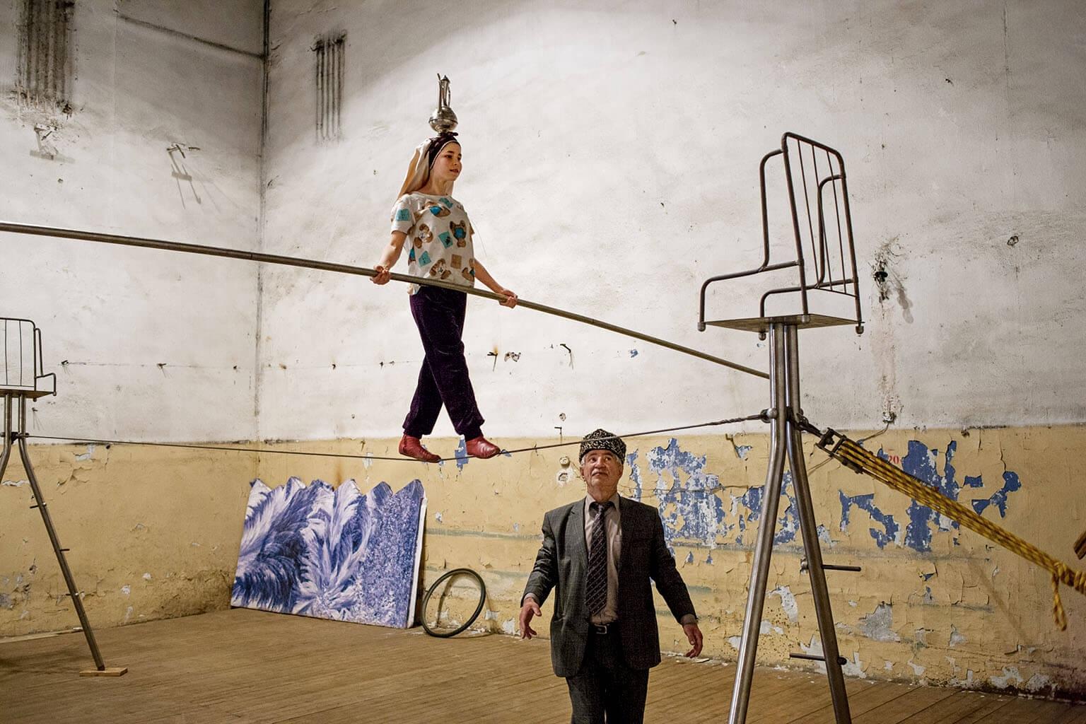 貝利萬馬戲團的創辦人阿斯哈巴里.戈薩諾夫是「達吉斯坦之鷹」的訓練員,他站在年僅13歲、頭頂著水壺表演的帕悌瑪.穆塔察利瓦下方待命以防萬一。攝影:傑赫米.榮格 JÉRÉMIE JUNG