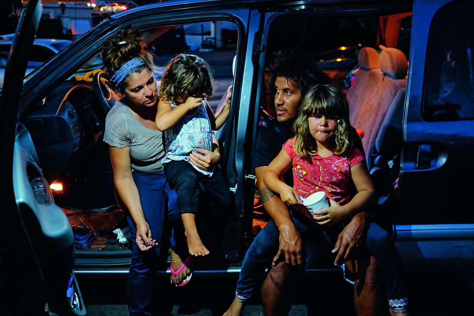 在聖地牙哥市金嶺住宅區的一座「安全停車場」,蘿拉.齊塔姆抱著女兒溫蕾,德里克.亞歷山大抱著另一名較大的女兒梅貝爾,坐在他們兼以為家的廂型車中。這家人在2018年12月終於找到一間負擔得起的公寓。PHOTO: JOHN GASTALDO