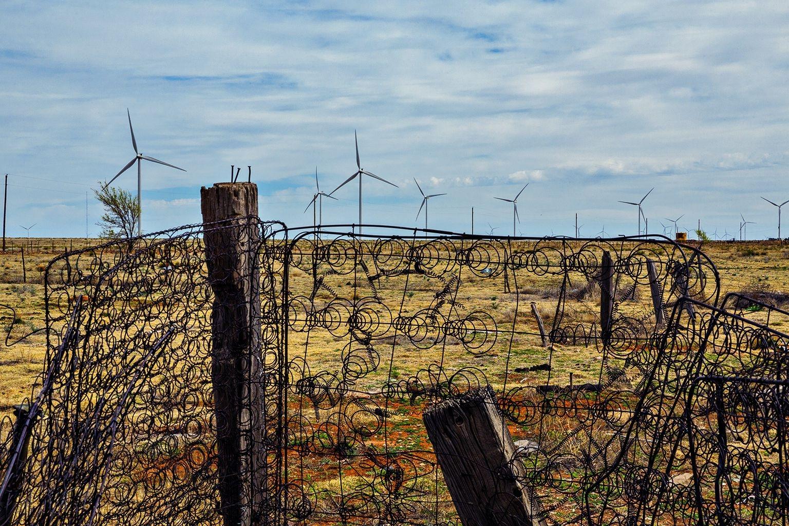 新墨西哥州伊利達鎮附近的這座舊圍欄是用床墊彈簧做成的。這裡的風力機利用高平原上無時止息的風力來發電,替那些因為水井乾涸而失去生計來源的農民帶來新收入。攝影:藍迪.奧森 Randy Olson