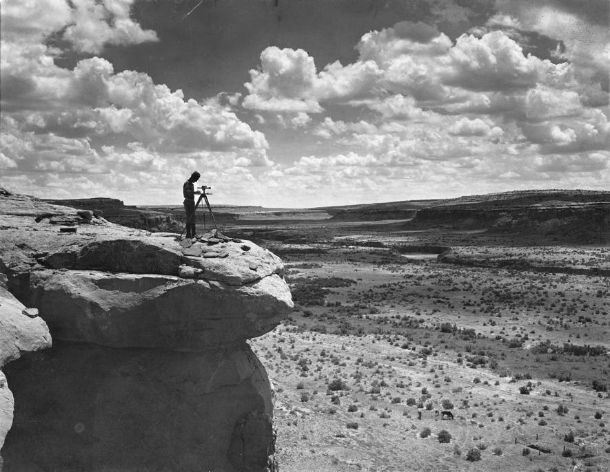 一名測量員站在峭壁上記錄查科峽谷的地形。PHOTOGRAPH BY NEIL M. JUDD, NAT GEO IMAGE COLLECTION