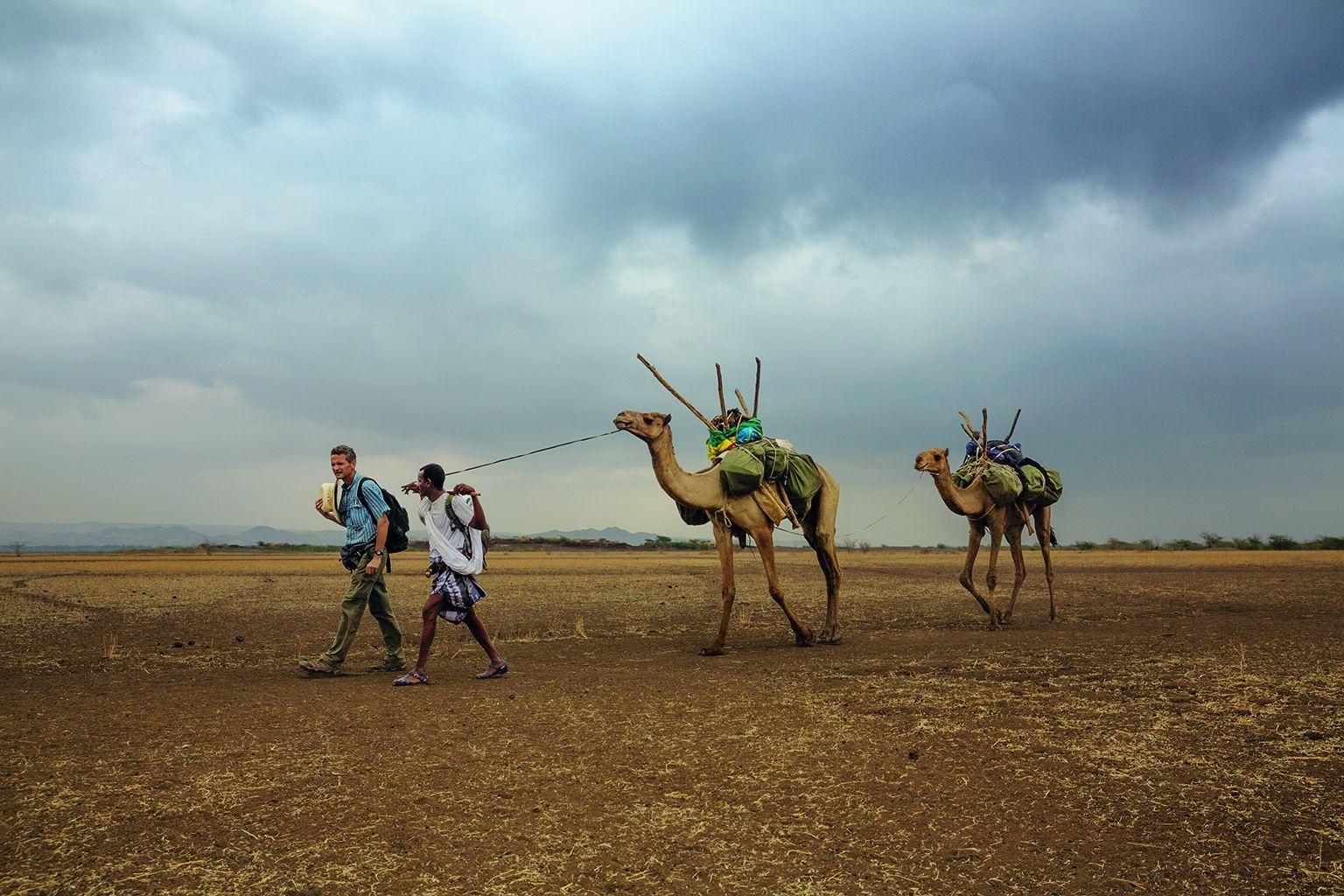衣索比亞,2013年。追隨先人的腳步。保羅.薩洛培克(左)和他的嚮導阿米德.艾勒瑪從赫托波里村展開了全球長征的第二天。體質特徵上最早的現代人就是從這裡拋下他們所熟悉的非洲地景,開始探索未知的世界。攝影:約翰.史坦邁爾 JOHN STANMEYER