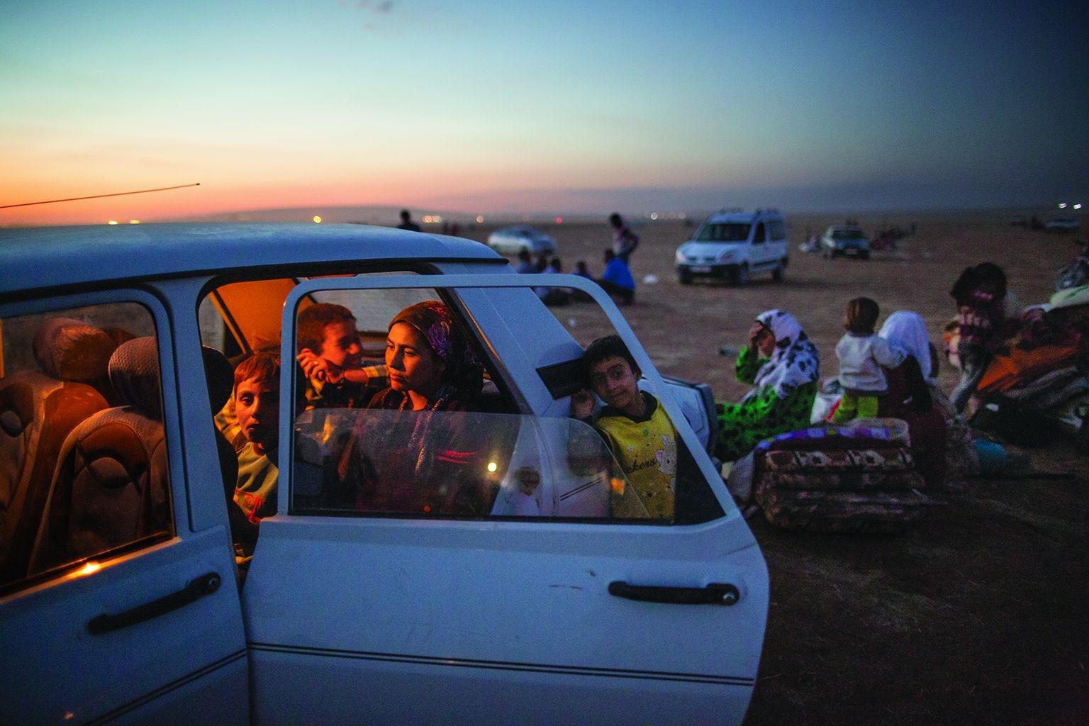 為了逃離伊斯蘭國的進逼,一個庫德族家庭逃出敘利亞後,在車中等待前往土耳其。2014年9月,有15萬名敘利亞人(大多是庫德族)花了72小時的旅程抵達土耳其。約翰.史坦邁爾 JOHN STANMEYER