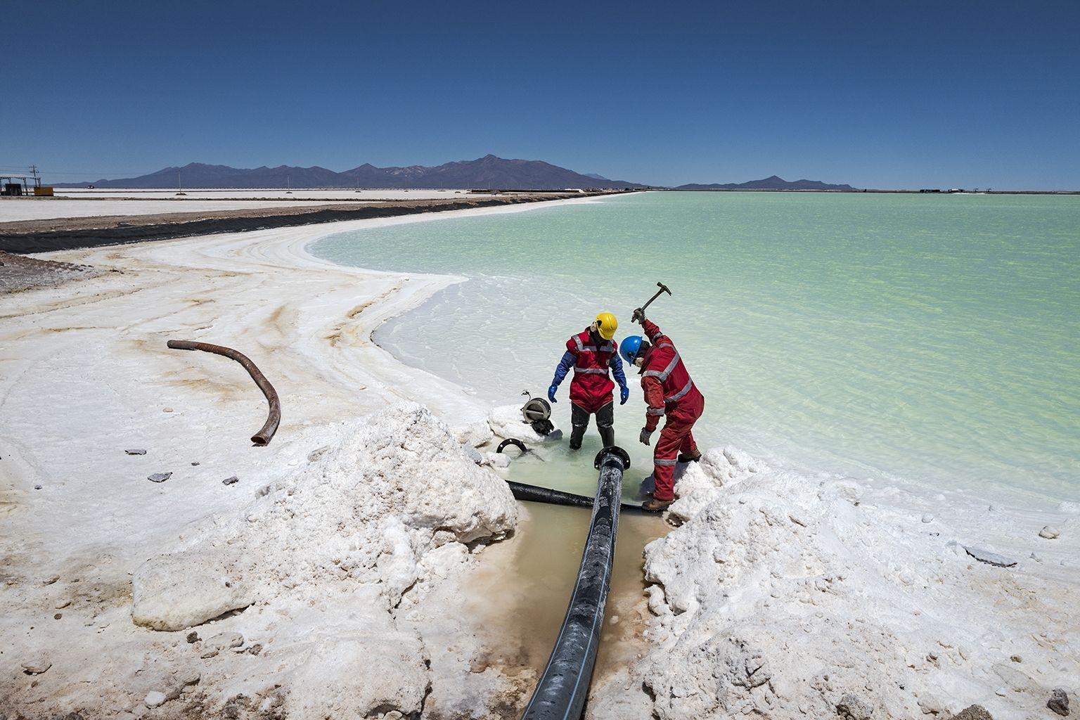 鋰工廠的工人使用鐵鎚擊碎一塊鹽層,因為鹽塊經常會阻塞將含有鋰的鹽水運輸到蒸發池的管線。乾燥的鹽則堆積在蒸發池四周。PHOTO: CÉDRIC GERBEHAYE