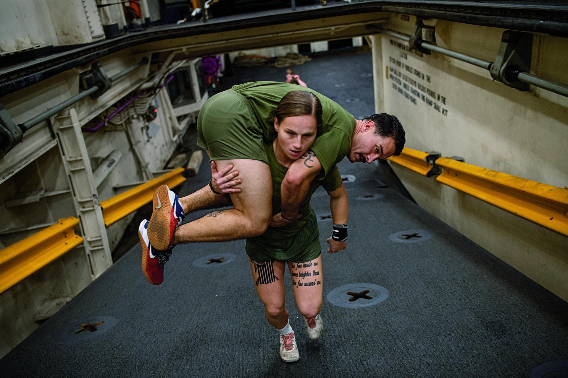 美國 必要時,海軍陸戰隊隊員必須能扛著同袍行動。在北卡羅萊納州勒瓊基地的海軍軍艦上,海軍陸戰隊下士嘉布里埃.格林扛起一位陸戰隊同袍準備上艦部署。每年有3萬8000名新兵加入海軍陸戰隊,其中約有3500人是女性──或用美國海軍陸戰隊的說法:「陸戰隊女兵」。攝影:琳西.艾達里歐 LYNSEY ADDARIO