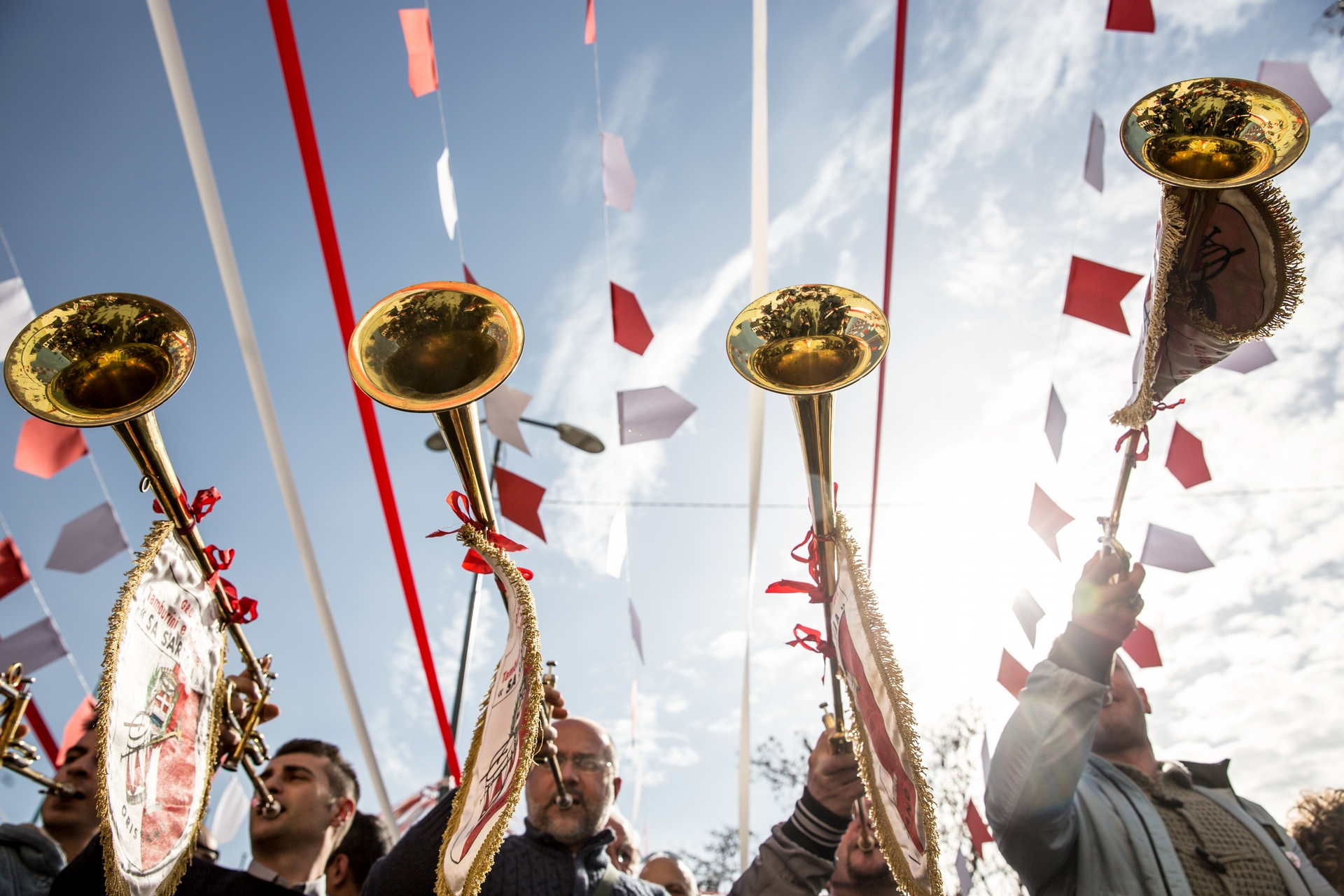 萬歲!我們有「康波里多利」了! - 薩爾提里亞節的每一個儀式都由小號和鼓伴奏。照片中,宏亮的小號聲宣佈工匠公會已抵達「蘇康波里多利」當選人的家中。他們會用由天主堂在聖燭節(Candlemas)清早祝福過的蠟燭來進行一場「授權」儀式。在聖燭節當晚,公會也會與「蘇康波里多利」共同舉辦一場對外開放的盛大派對。  PHOTOGRAPH BY MICHELE ARDU