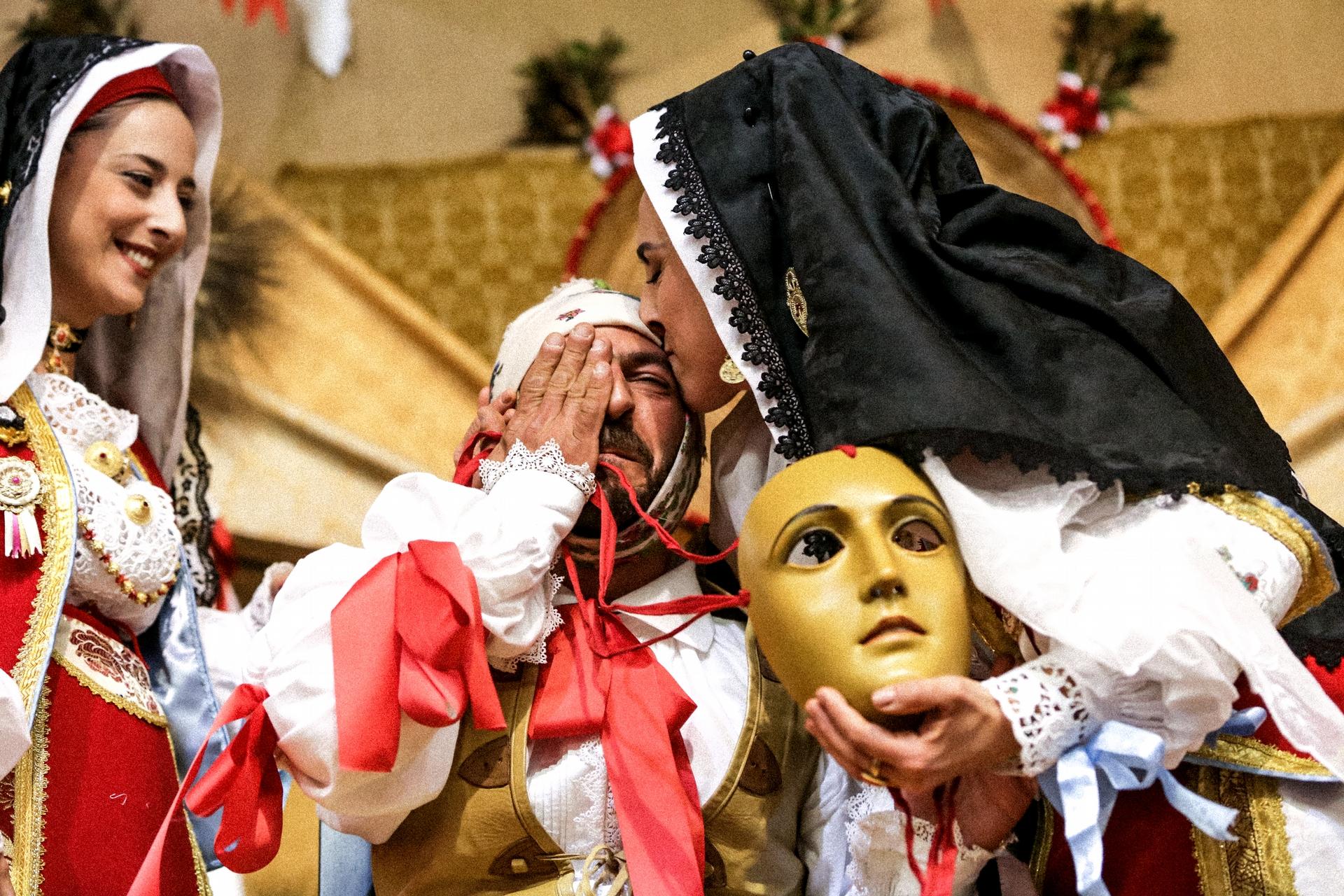 回到地上 - 能成為「康波里多利」不僅是薩爾提里亞騎士最崇高的榮譽,也是許多居民的終身夢想。當選人只要戴上面具,就會化身為「康波里多利」。此時他的個人身分已不重要,因為他已變成奧里斯塔諾文化中最具代表性的人物。「康波里多利」必須全天禁食,雙腳也不能觸地;據說這麼能為社區帶來福祉和繁榮,並驅逐飢荒和瘟疫。照片中,塞吉歐.萊達在慶典結束後摘下面具,並返回「現實」。 他的妹妹埃利奧諾拉.萊達(Eleonora Ledda)為他獻上一個吻。埃利奧諾拉本身也是名隨著隊伍前進的「馬薩伊達斯」。 PHOTOGRAPH BY MICHELE ARDU