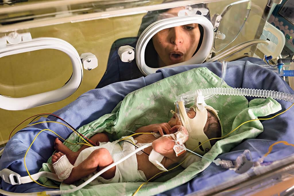 母親的聲音 在義大利摩德納的大學醫院新生兒加護病房中,克里斯汀娜.伊歐薩對早產的兒子亞利桑卓唱歌。父母親現在更常出現在新生兒加護病房中。「母親對孩子發出的聲音是最原始的精準醫學,因為那是只對孩子發出的聲音。」奧司塔與日內瓦谷地大學的研究員曼奴耶拉.菲利帕說。科學家推測,母親的聲音能夠刺激新生兒的腦部,讓詮釋聲音、了解語言的能力發育健全。  COMPOSITE: CRAIG CUTLER (HAND WITH CHIP); SAMUEL SANCES, CEDARS-SINAI (BACKGROUND)