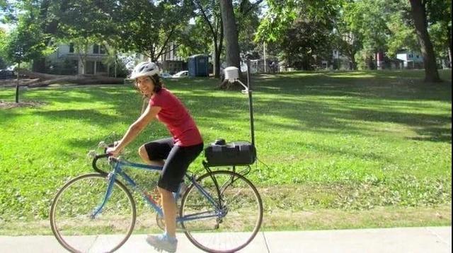 卡莉.茲特爾(Carly Ziter)在做研究時,把一個小氣象站綁在自行車後座上,騎著自行車在麥迪遜市附近轉圈。圖片來源:Carly Ziter/University of Wisconsin-Madison