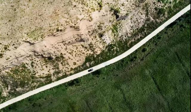 在中國西北部陝西省榆林市橫山區,一輛汽車行駛在一條將光禿禿的沙漠和被控制的沙漠分隔開來的路上。圖片來源:新華網