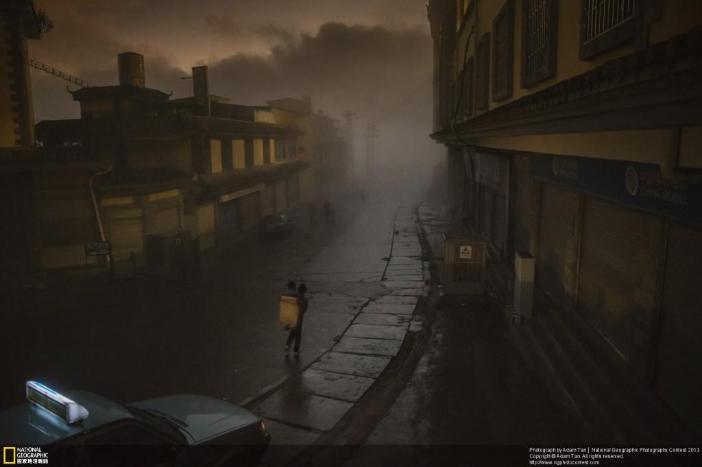 「2013國家地理攝影大賽」地方類首獎作品「長夜漫漫路迢迢」(Long Road to Daybreak)。照片中這座老城即將在中國快速的經濟成長下改頭換面,也許很快就會失去它素樸的美感。因此,我很高興自己在2012年一個有著濃霧的清晨,捕捉到這位上班媽媽用竹簍背著孩子,穿越迷霧行走的一幕。攝影師:亞當‧譚