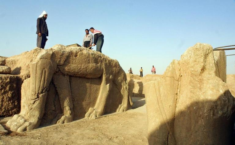 2001年7月,伊拉克工人在尼姆魯德考古遺址清理一座有翅膀的牛雕像。 Photograph by Karim Sahib, AFP, Getty Images