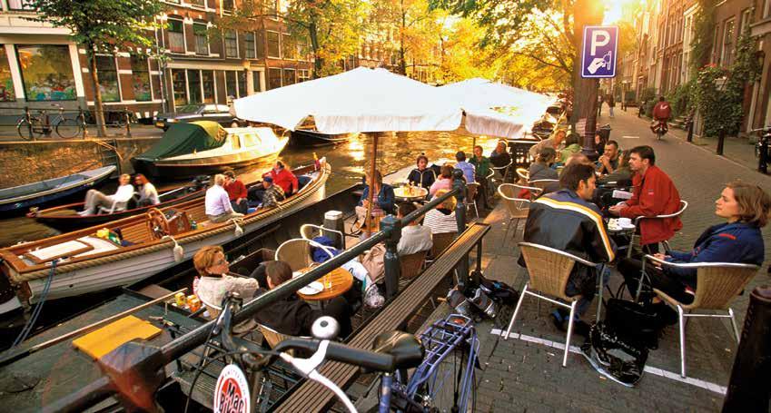 阿姆斯特丹運河沿岸沐浴在陽光中的露天咖啡館。圖片出自《全球220大最佳旅遊城市》