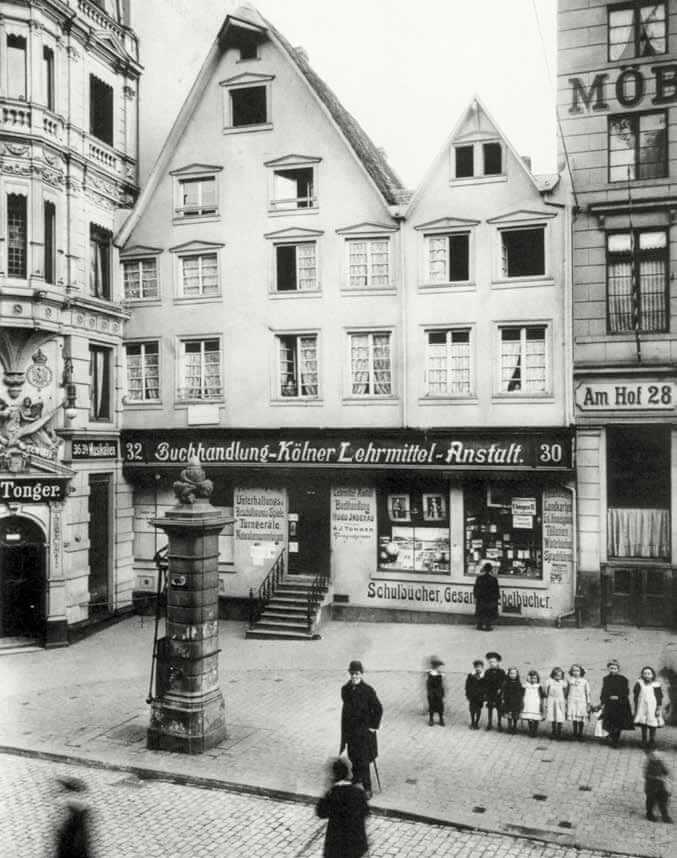 在這張1902 年的照片裡,小朋友在科隆(Cologne)教學協會 書店外面排成一列,一名顧客正在瀏覽櫥窗內的陳列品。左邊可以看到通格(Tonger)樂譜店。