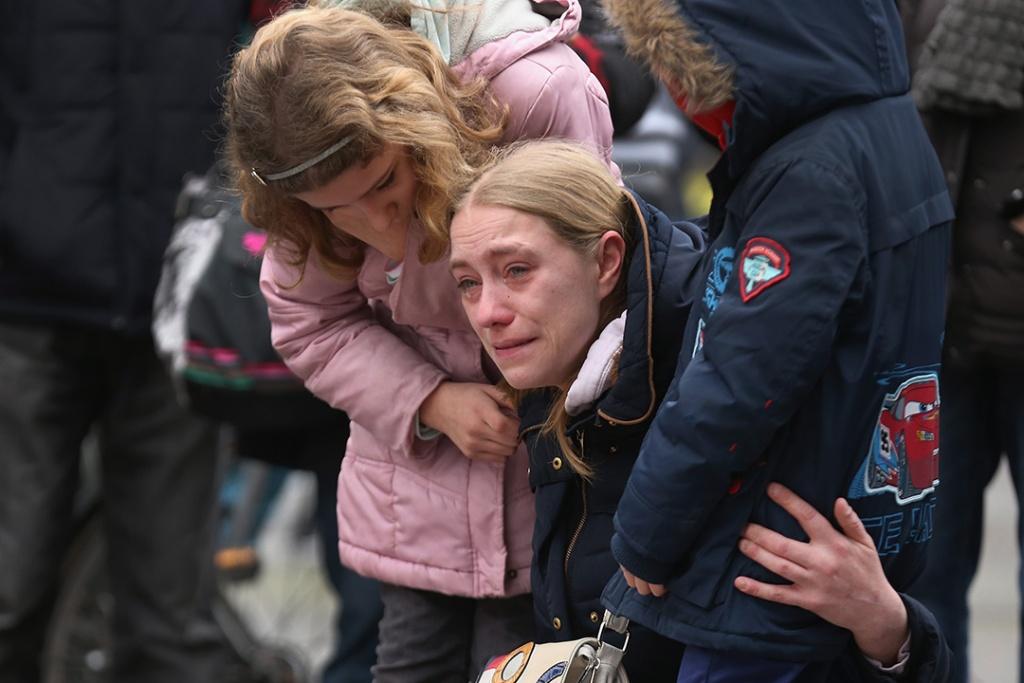 2016年3月23日,比利時,恐襲發生翌日,布魯塞爾交易所廣場有民眾舉行悼念活動,一名母親擁著她的孩子,跪在地上落淚。攝:Christopher Furlong/GETTY