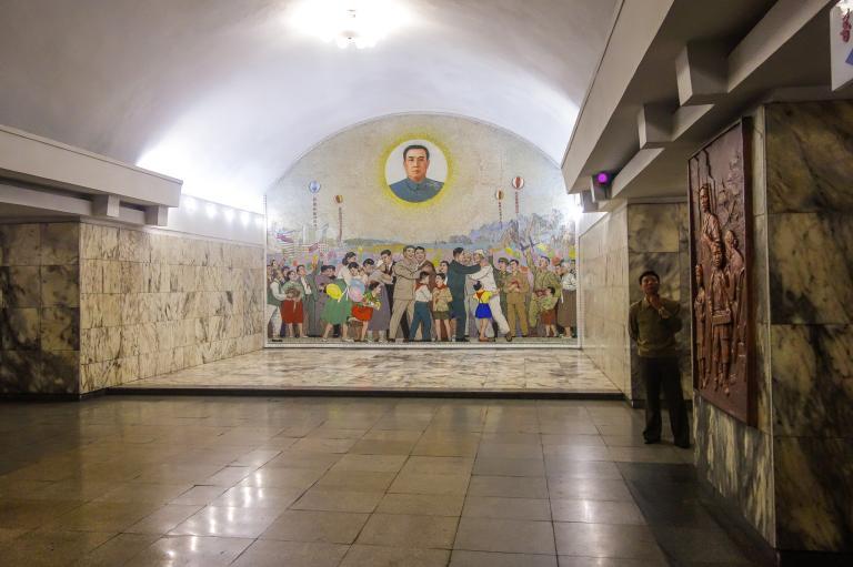 統一站的一幅壁畫描述了這個國家未來的夢想。帶領北韓脫離日本獨立的建國領導人金日成在畫中成了太陽,凝視著南北韓人民慶祝統一的歡樂景象,而統治者當然仍然是北韓政府。PHOTOGRAPH BY ELLIOTT DAVIES