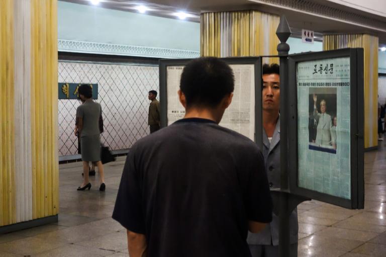 月台上用框裱著的國營報紙。乘客在等車空檔利用時間閱讀新聞。PHOTOGRAPH BY ELLIOTT DAVIES