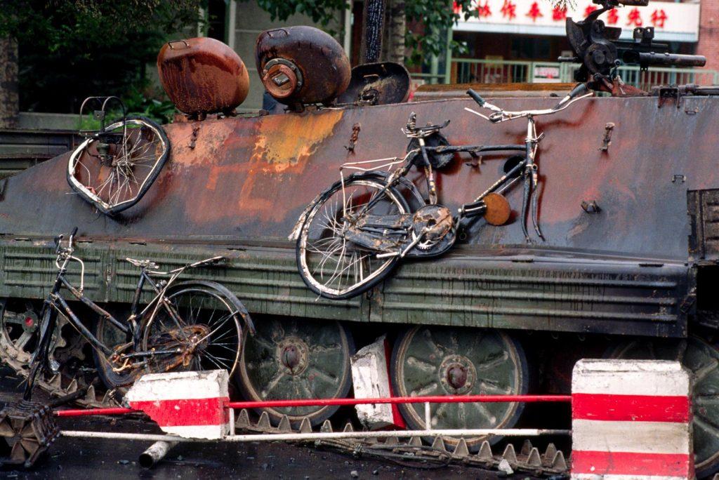 解放軍坦克欲進入天安門廣場時,被學生放火試圖阻止攻勢;扭曲變形的腳踏車掛在上頭。