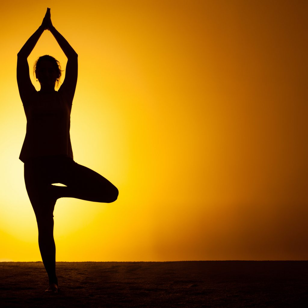The silhouette of woman practicing yoga in the sunset light