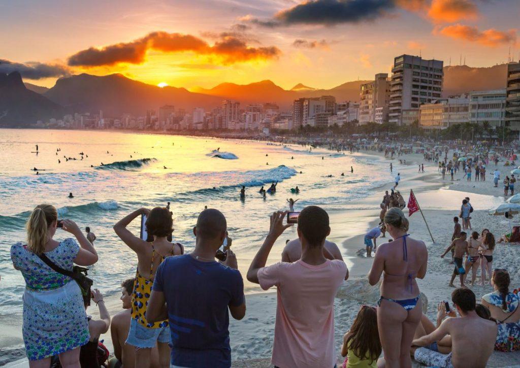 遊客們在里約熱內盧的伊帕內瑪海灘(Ipanema Beach)拍攝夕陽美景。PHOTOGRAPH BYJON HICKS, GETTY IMAGES